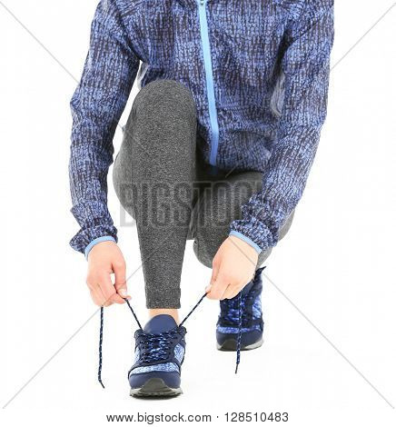 Sporty woman tying shoelaces isolated on white
