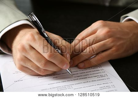 Male hand with pen signing document at the desk closeup