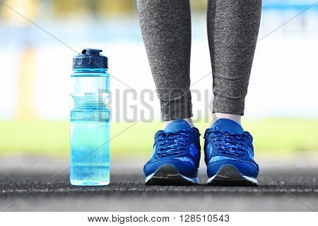 Woman in sports clothes and sneakers with bottle outdoors