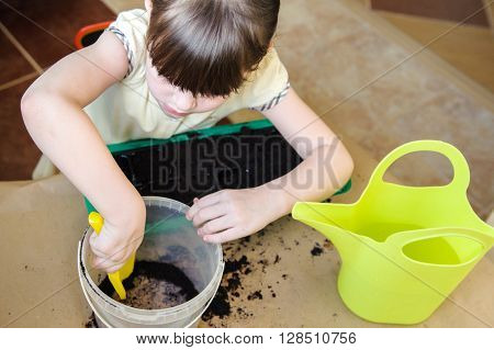 Beautiful girl in a yellow dress holding a shovel and gaining ground from its bucket