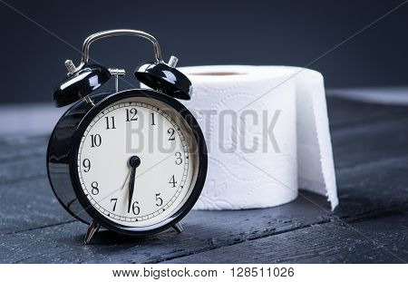 Alarm Clock With Toilet Paper On A Table