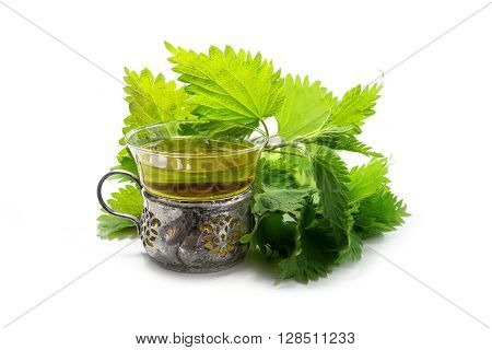 nettle tea in a cup of glass and silver fresh branches and leaves isolated with shadows on a white background a medicinal herb from the pharmacy of nature selected focus narrow depth of field