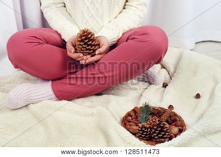 Woman with pine cone and wicker decoration basket, closeup