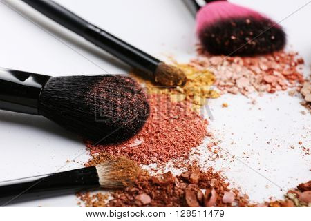 Makeup brushes with cosmetic powder on white background