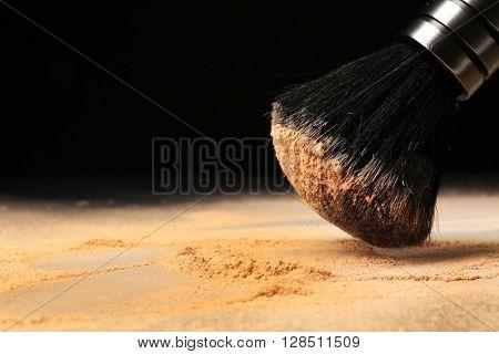 Make up brush and powder on black background