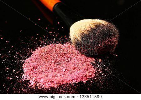 Make up brush and pink blusher on dark background