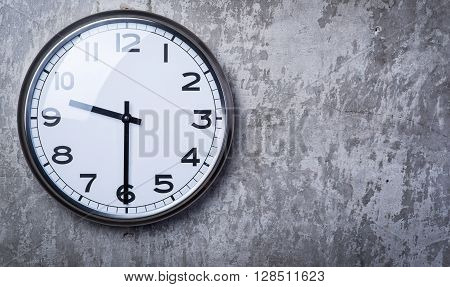 Round Wall Clock Hanging On The Grey Concrete Wall