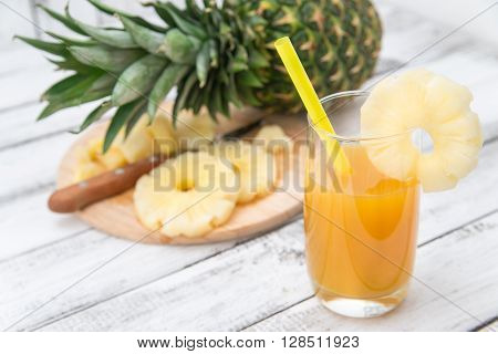 pineapple juice in glass on a wooden rustic table