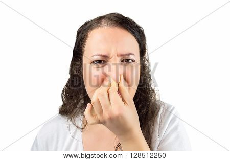 cropped image of a woman covering her nose and mouth with her hands looking at the camera in concept of disgust and there is a bad smell over a white background