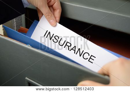 Business woman seeking an insurance policy in a filing cabinet
