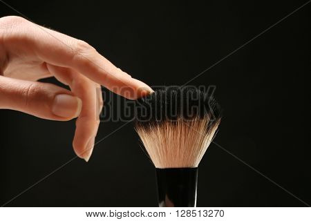 Female hand touching professional makeup brush hair on black background