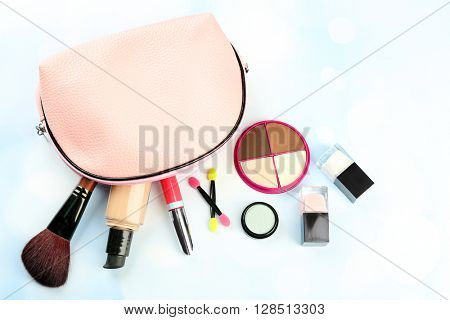 Makeup set with beautician, brush and cosmetics on blue blurred background