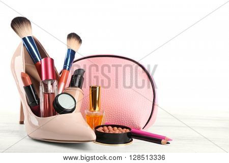 Makeup set with beautician, beige woman's shoe, brushes and cosmetics on light background