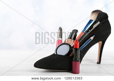 Makeup set with black woman's shoe, brushes and cosmetics on white background