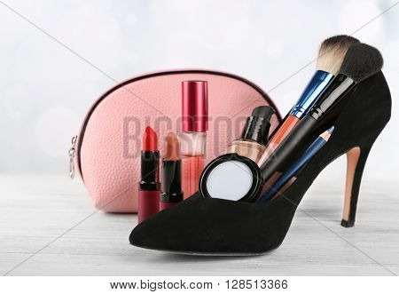 Makeup set with black woman's shoe, beautician, brushes and cosmetics on light background