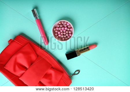 Beauty case and lipsticks for makeup on turquoise background
