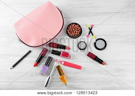 Makeup set with beautician and cosmetics on white wooden  background