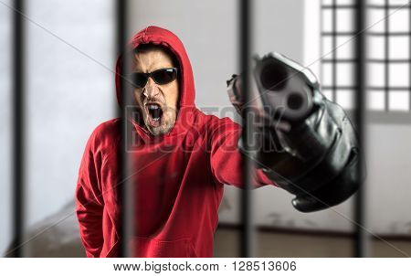 gangsman with gun in a threatening tone at the cell of a prison