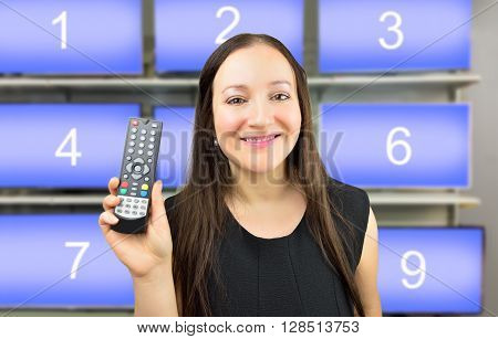 Closeup of a woman holding a remote control with channel numbers in background