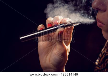 Close up of a woman inhaling from an electronic cigarette.