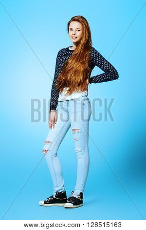 Full length portrait of a happy teenager girl in casual clothes looking at camera and smiling. Modern teen generation. Youth fashion. Healthy hair, haircare.