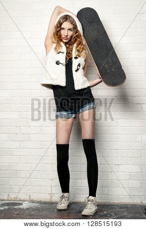 Trendy teen girl with bright foxy hair alluring with her skateboard by a brick wall. Youth fashion.