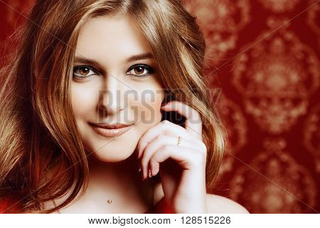 Close-up portrait of a beautiful young woman with magnificent wavy hair and evening make-up smiling at camera.