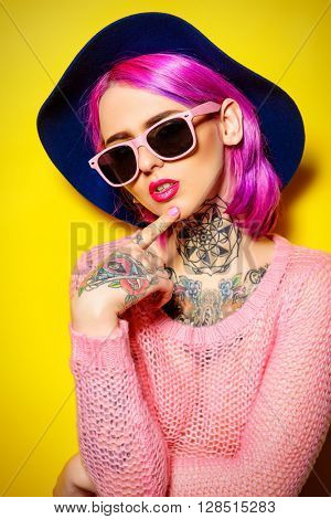 Pretty girl with crimson hair wearing bright clothes and sunglasses posing over yellow background. Bright style, fashion. Optics style. Tattoo.