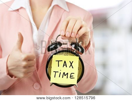 Tax concept. Woman in pink suit holding alarm with tax time inscription