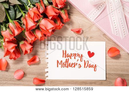 Bouquet of fresh pink red roses with gift on wooden background. Floral romantic arrangement with card text Happy Mother's Day.