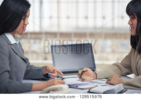 side view of friendly businesswomen discussing and consulting document