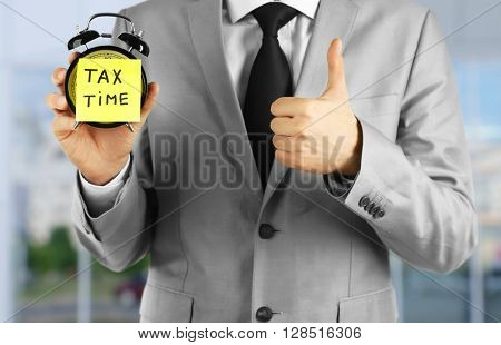 Tax concept. Businessman holding alarm clock, tax time