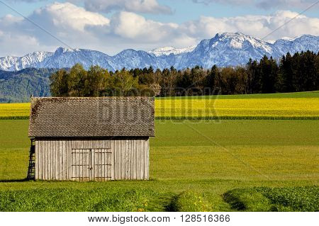 Hut Standing On The Meadows In Front Of Mountains