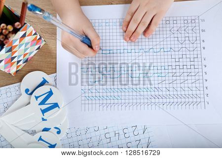 Little girl learning to draw at the table
