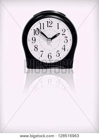 Alarm clock with reflection on white background.Purple toned image.