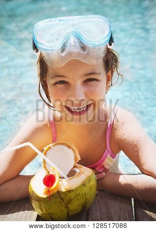 Cute funny little girl wearing swiming mask drinking coconut at the pool. Summer vacation concept