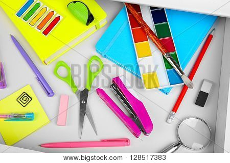 Stationery in open desk drawer, top view