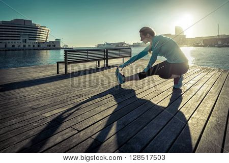 Woman do exercise after running on the wooden pier under sunlight.