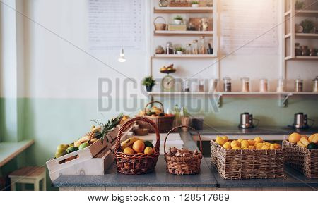 Fruit juice bar counter with fruits in basket.