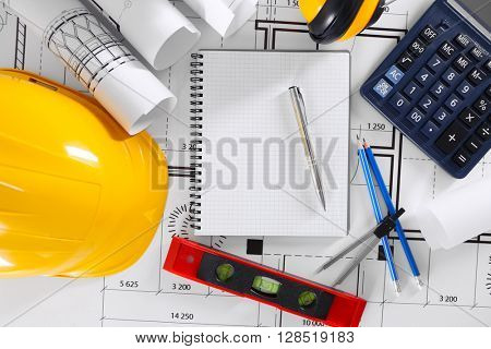 Construction blueprints with tools and helmet, top view