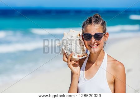 Summer vacation. Listening to the sea - beautiful girl with shell at the beach