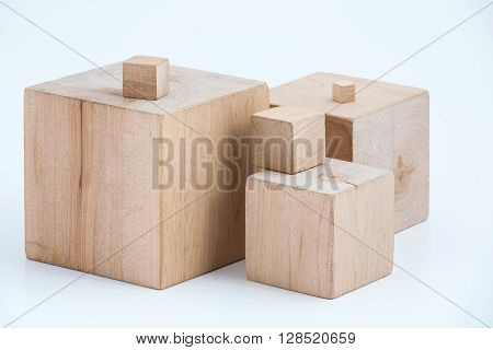 Group of wooden cubes of the different sizes. Subject shot in studio on a white background.