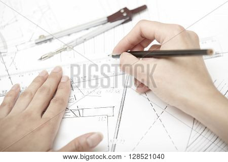 Hands of engineer working on a construction plan