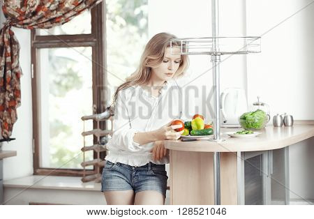 Blond lady at kitchen preparing vegetable for breakfast