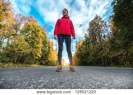 Lady in a track suit standing on the road with trees