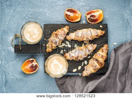 Italian style home breakfast. Latte coffee, almond croissants and red bloody oranges on dark wooden serving  board over concrete textured table, top view, horizontal