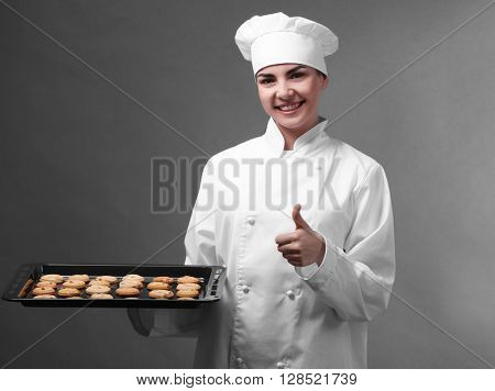 Satisfied professional cook holding oven-tray with cookies on grey background