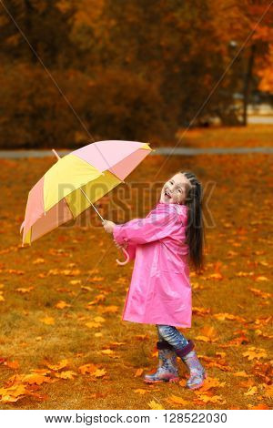 Beautiful little girl with umbrella in park