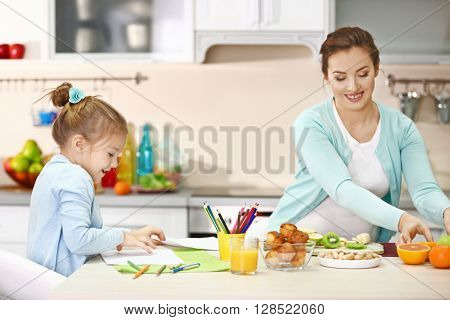 Pregnant woman making dinner while her daughter painting