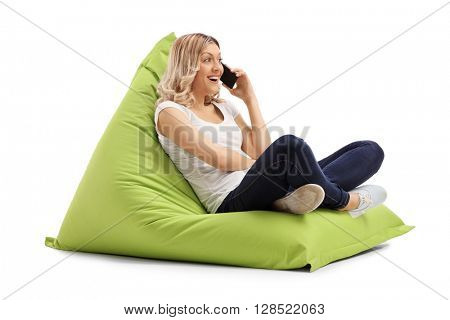 Young joyful woman talking on cell phone seated on a green beanbag isolated on white background